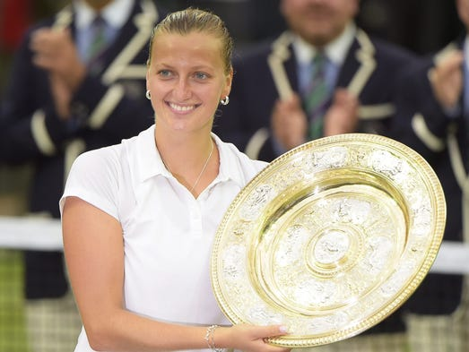 Petra Kvitova of Czech Republic holds the championship trophy following her victory over Eugenie Bouchard of Canada.