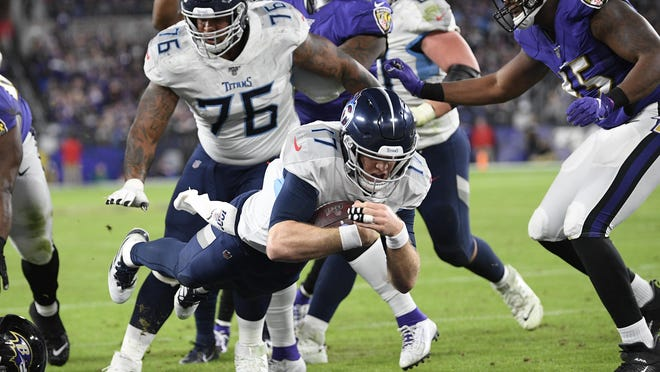 Tennessee Titans quarterback Ryan Tannehill leaps to the end zone for a touchdown against the Baltimore Ravens during the second half of an NFL divisional playoff football game on Saturday