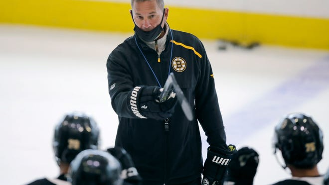 Boston Bruins head coach Bruce Cassidy talks with his players at the NHL hockey team's camp on Tuesday, July 14, 2020, in Boston.