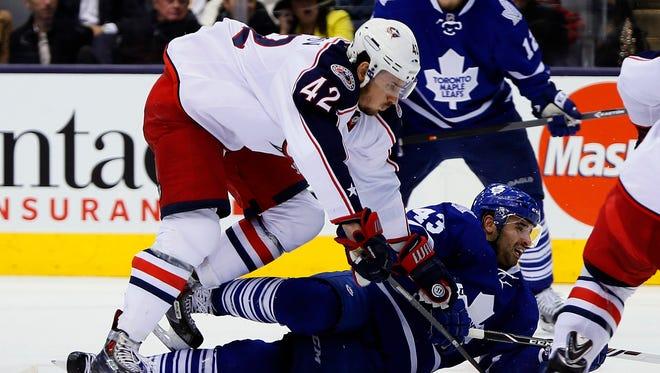 Columbus Blue Jackets forward Artem Anisimov (42) takes down Toronto Maple Leafs forward Nazem Kadri (43) during the third period at the Air Canada Centre.