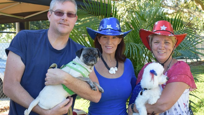 Retired U.S. Army Staff Sgt. James Taylor, left, and his PTSD service dog Pia-Pia, with Dogs for Life supporter Kathi Schumann and Dogs For Life CEO/Founder Shelly Ferger holding her dog, Sunny, at the 2016 Howl-O-Ween Dog Costume Pawrade in Vero Beach.