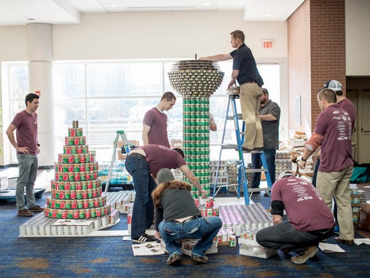 A team builds a structure made of canned food for this