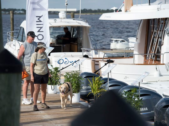 Cliff Abrams (from left), L.A. Abrams and Darel the dog browse the selection at the 44th annual Stuart Boat Show on Friday, Jan. 12, 2018 along Old Dixie Highway in Stuart. The show features over 200 exhibitors selling boats, accessories, clothing, jewelry, fishing gear and more. The show continues 10 a.m. to 6 p.m. Saturday and 10 a.m. to 5 p.m. Sunday. For more information, go to stuartboatshow.com.