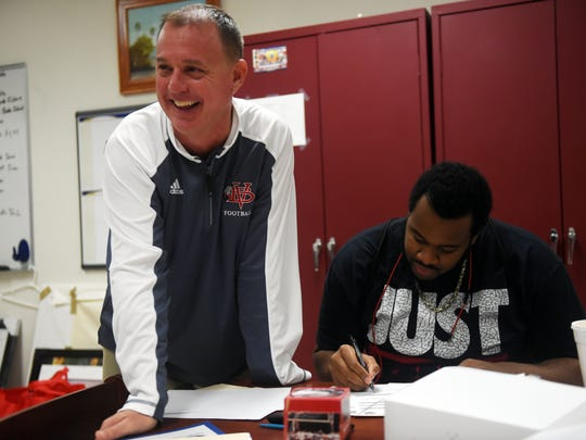 Vero Beach High School head football coach Lenny Jankowski shares a laugh with Jarvis Jones early Wednesday, Feb. 7, 2018 as Jones signs his letter of intent to play football with Highland Community College (Kansas) on National Signing Day. The 6-foot-4, 315-pound Jones was a first-team all-area selection as a senior and is rated a two-star recruit by 247Sports.