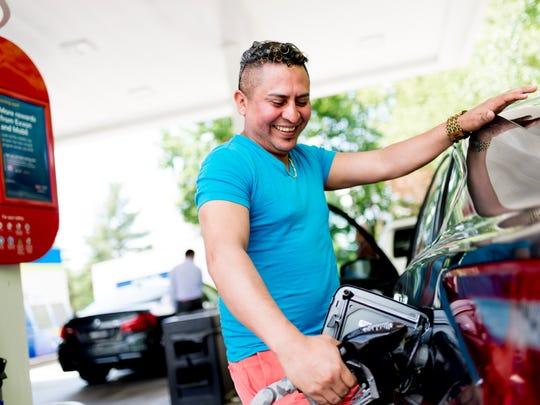 Marlon Reyes, of Atlanta, fills up his car while traveling