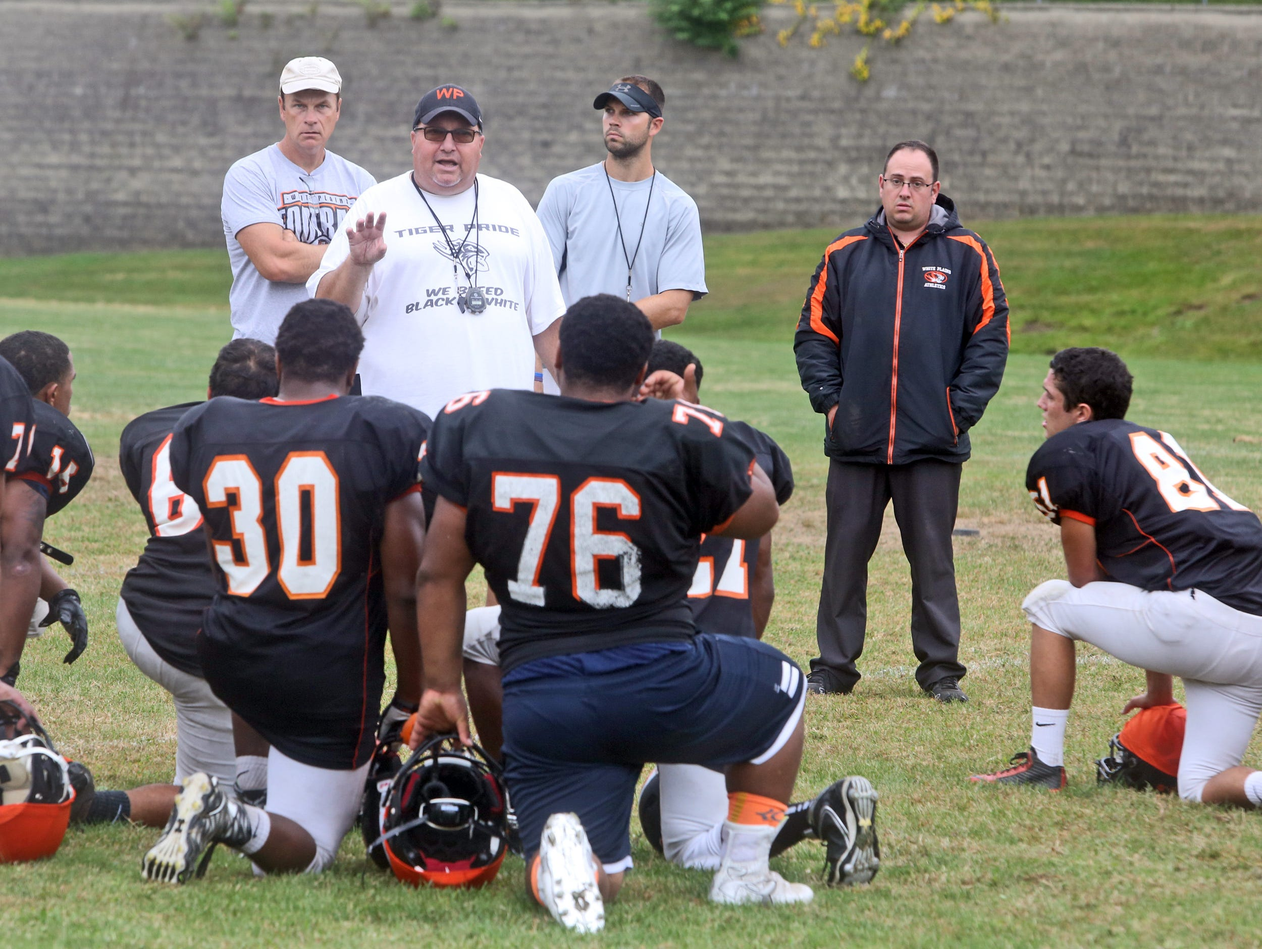 Mike Mirabella, the athletic trainer at White Plains High School, standing at right, looks in on varsity football practice Sept. 29, 2015.