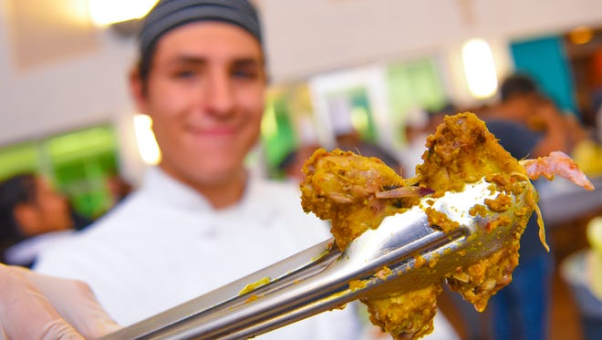 Guam Community College culinary student Drew Acree offers  pieces of spicy chicken wings to taste during the 2018 Pastries in Paradise at the Guam Museum in Hagåtña on Thursday, Feb. 22, 2018.