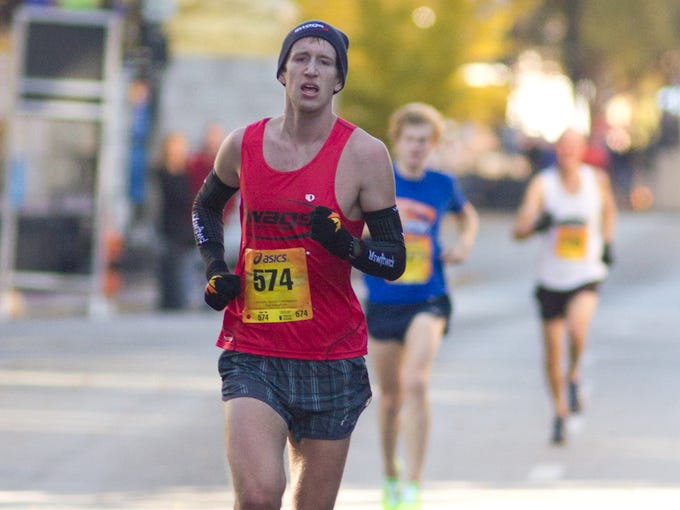 Michael Eaton leads the pack down Main Street during the Louisville Sports Commision Half MArathon. Eaton won the mens division of the race with a time of one hour and twelves minutes.  November 10, 2013.