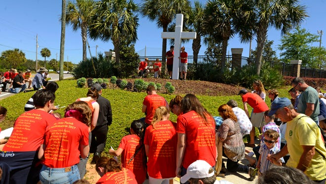 Members of St. Ann Catholic church and others hold a Palm Sunday Stations of the Cross procession in Gulf Breeze last April. The group stopped to observe the different stations of the cross leading to the crucifixion of Jesus Christ. The procession started and ended at St. Ann Catholic Church.