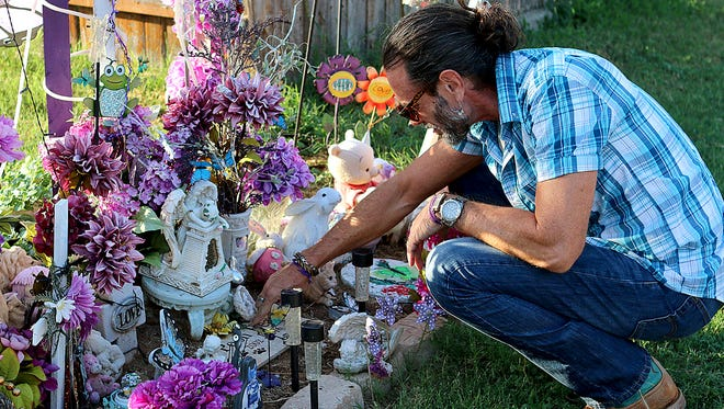 Vern Landavazo cleans off a marker left at a memorial for his daughter, Lauren Landavazo, on Aug. 28. Lauren was murdered on Sept. 2, 2016 walking home from school.