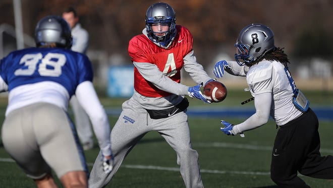 University of Memphis quarterback Riley Ferguson (center) hands off to Darrell Henderson during drills at the  Billy J. Murphy Athletic Complex Tuesday morning as the team prepares for the upcoming Liberty Bowl against Iowa State.