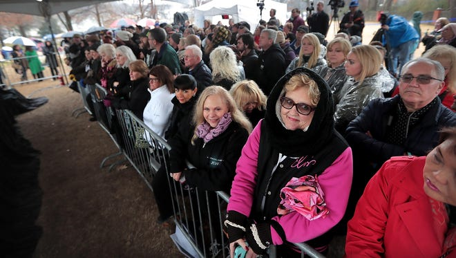 Fans attend what would have been Elvis PresleyÕs 83rd birthday at Graceland on Monday. Several hundred fans huddled in the rain on the front lawn of PresleyÕs mansion to serenade the King with the sounds of ÒHappy BirthdayÓ during the annual celebration.