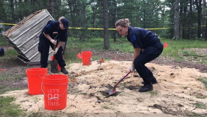Michigan State Police Crime Lab technicians work the scene of a supposed homicide victim's grave in Hale, Mich.