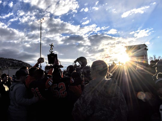 The blue championship trophy glints in the setting sun at Tiger Stadium as Capitan fans, coaches and players celebrate their victory.