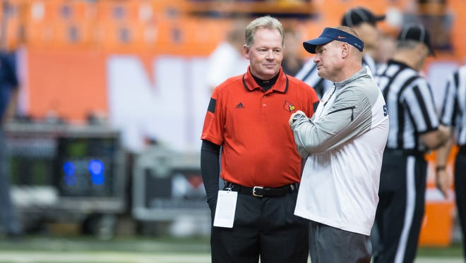 SYRACUSE, NY - OCTOBER 03:  Head coach Bobby Petrino of the Louisville Cardinals and head coach Scott Shafer of the Syracuse Orange talk before the start of a football game on October 3, 2014 at the Carrier Dome in Syracuse, New York.  (Photo by Brett Carlsen/Getty Images)
