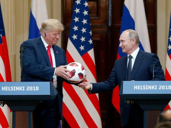 Vladimir Putin gives Donald Trump a soccer ball from