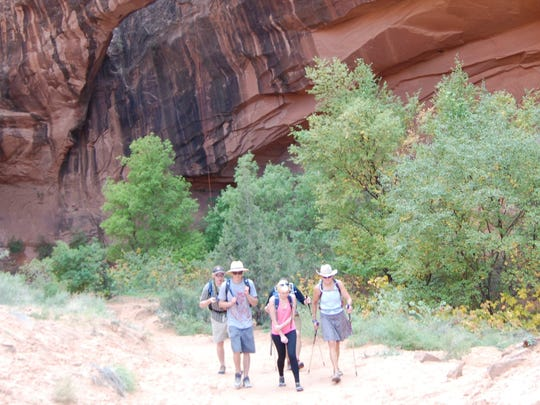 In this Oct. 29, 2013, photo, people walk near Morning Glory Arch near Moab, Utah., in Negro Bill Canyon. The renewed national scrutiny of the Confederate flag has officials again considering changing the name of Utah's Negro Bill Canyon, though the title that some find offensive is a point of historical pride for others.