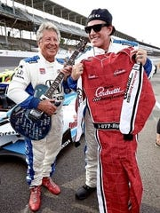 Mario Andretti, left, and Neal Schon exchange gifts at Indianapolis Motor Speedway in 2015.