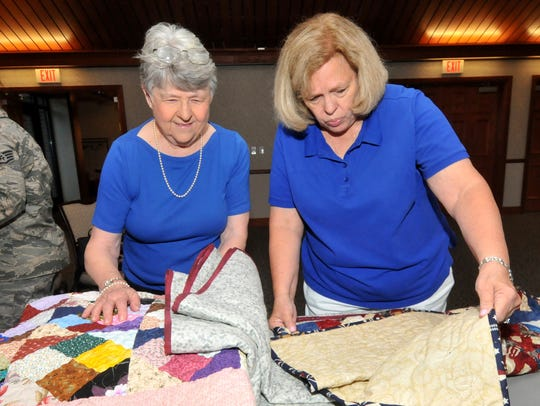 Sherry Brown, left, and Susan Darmo fold quilts for