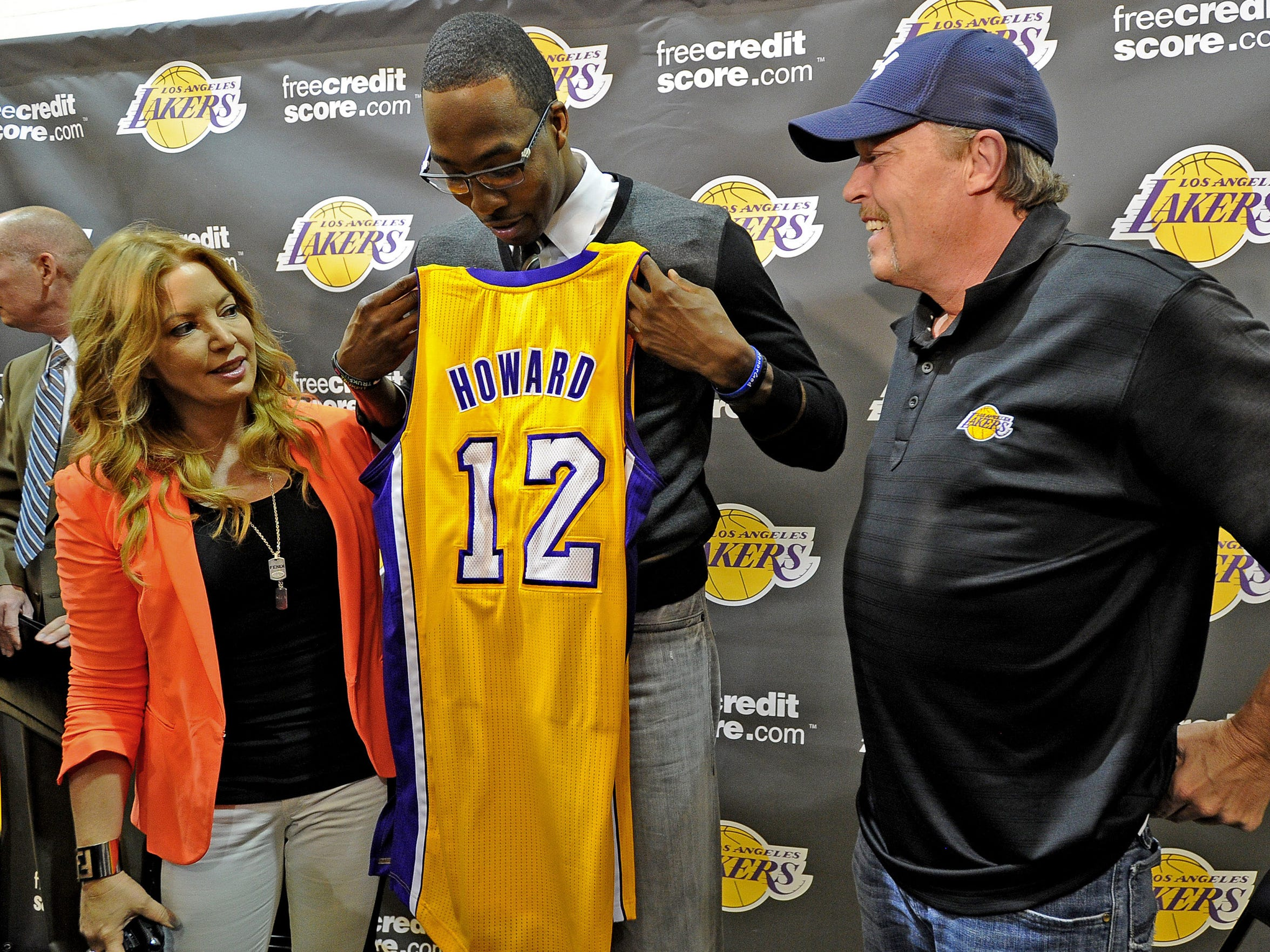 Jeanie Buss and Jim Buss welcome Dwight Howard in 2012 as he holds his jersey during a press conference held to introduce the three-time defensive player of the year who was acquired in a four-team trade from the Orlando Magic that offseason.