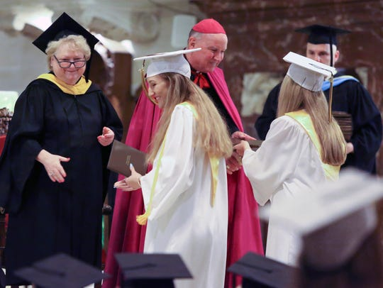Cindy Mann, Padua Academy's head of school, and Bishop Francis Malooly greet Padua graduates as they receive their diplomas at St. Anthony of Padua in Wilmington in 2016.