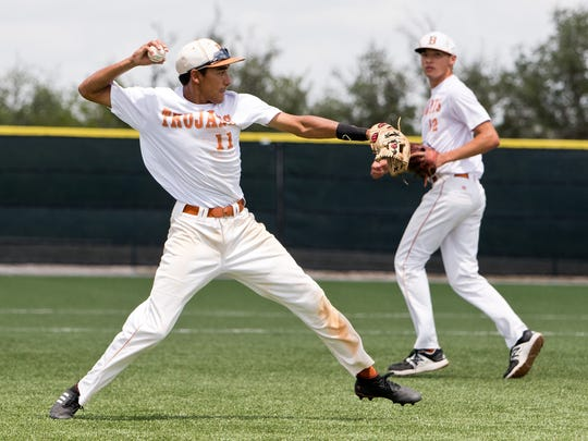 Beeville third baseman Joaquin Garza (left) throws to first for an out for the Trojans as pitcher Justin Gomez looks on during the team's 14-1 win over Orange Grove in the second game of a best-of-three regional quarterfinal series in the 4A postseason Saturday afternoon at Joe Hunter Field in Beeville.