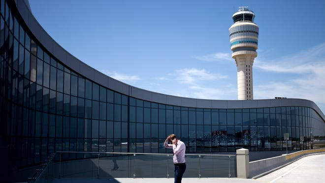 A passenger paces while on the phone outside the Maynard Jackson International Termain at the the Hartsfield-Jackson Atlanta International Airport on April 26, 2013.