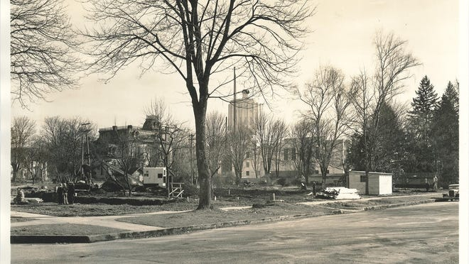 The Oregon State Capitol, under construction, is seen from the intersection of Winter and Chemeketa streets NE. The house in the foreground was the Cooke-Patton House, which was demolished to make way for the state library.