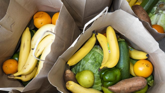 Fruits and vegetables fill grocery bags at a food distribution event for people in need.