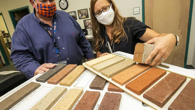 Marion County Public Schools facilities employees Mike Robey, construction coordinator, and Ivonne Bumbach, design coordinator, look at brick samples on Monday for a construction project. School officials fear K-12 budgets could get cut in the fall.