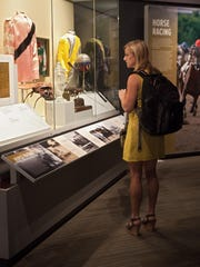 A visitor looks at the display case in the Louisiana Sports Hall of Fame museum showcasing the state's fabled jockeys and horses and tracks.