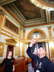 Eileen Grogan, left, of Conrad Schmitt Studios, Vic Williamson, rear, of Rogers Krajnak Architects, and bailiff Dan Hoover evaluate the interior of the west courtroom in the Licking County Courthouse for possible restorations.