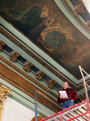 Vic Williamson of Rogers Krajnak Architects evaluates the interior of the west courtroom in the Licking County Courthouse for possible restorations.