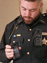 Coshocton County Deputy Sheriff Wesly Wright Eppley demonstrates the use of new body cameras. The device attaches to his uniform, records video and audio, captures photographs, and acts as a wireless microphone for his radio. He can remove the device to manage content and to turn it  around while in use so others can see themselves being recorded.