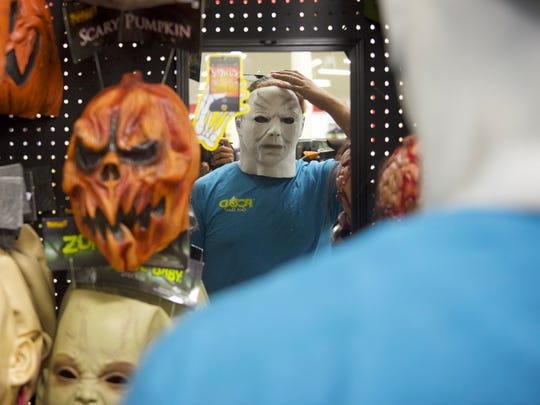 Kane Covington tries on a mask at the Spirit Halloween store on Thursday, October 20, 2016.