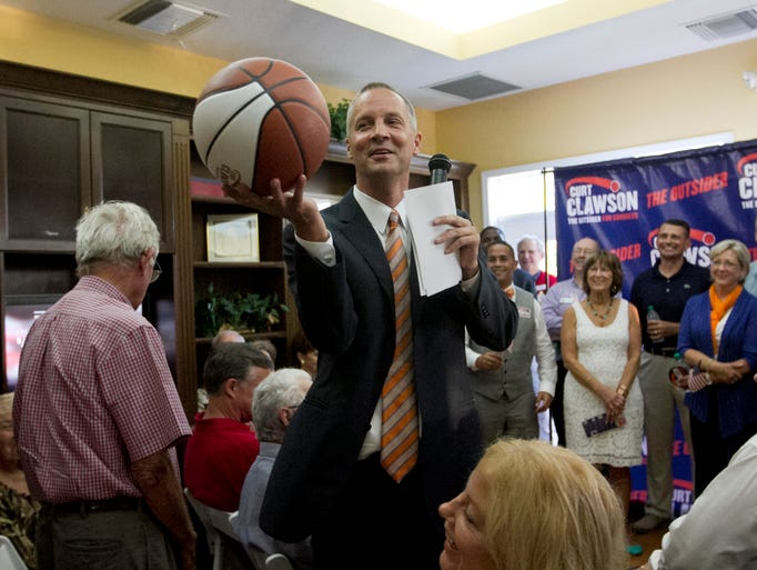 Curt Clawson grabs a basketball from the crowd while speaking at his election party Tuesday in Bonita Springs.