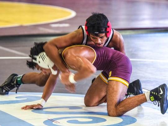 Tiyan Titans' Kenneth Malsol Jr., top, jockeys for better leverage during his match with Father Duenas Memorial School Friars' Devon Garrido at the Phoenix Wrestling Club's Preseason Wrestling Invitational held at the Mangilao school on Staurday, Nov. 11, 2017.