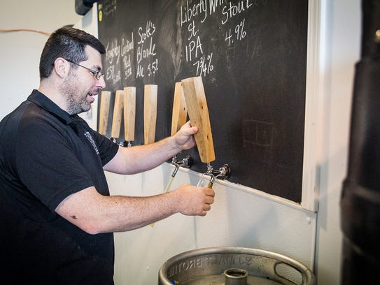 Sean Brady pours a beer at his New Corner Brewing Co.