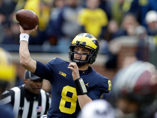 Michigan quarterback John O'Korn throws during the