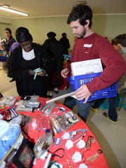Jarrett Barnett helps Stephanie King pick out holiday gifts at the Common Ground Christmas Market.