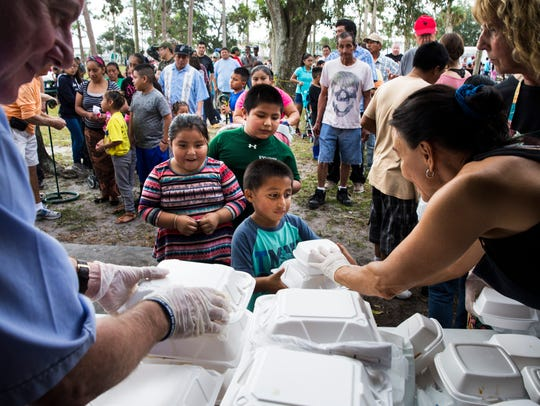 Children receive hot meals from volunteers on Thanksgiving