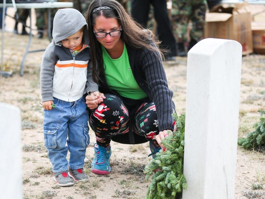 Megan Bates and Burke Bates, 2, lay a wreath on a grave