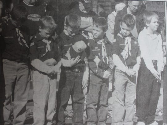 Boy Scouts bow their heads in prayer during the Veteran's Day services held in front of the court house in 2005.