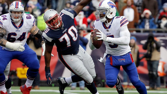 Buffalo Bills quarterback Tyrod Taylor (5) scrambles away from New England Patriots defensive tackle Adam Butler during the first half of an NFL football game, Sunday, Dec. 24, 2017, in Foxborough, Mass.