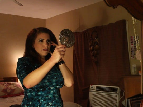 Kimberly Cardenas holds up a mirror in a still from