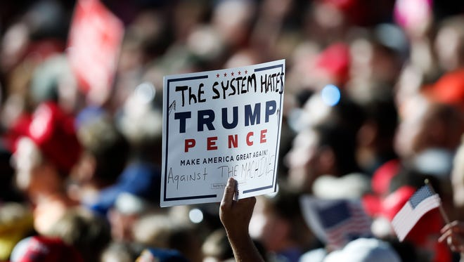 A supporter of Republican presidential candidate Donald Trump holds a sign during a campaign rally Thursday, Nov. 3, 2016, in Selma, N.C. (AP Photo/John Bazemore)