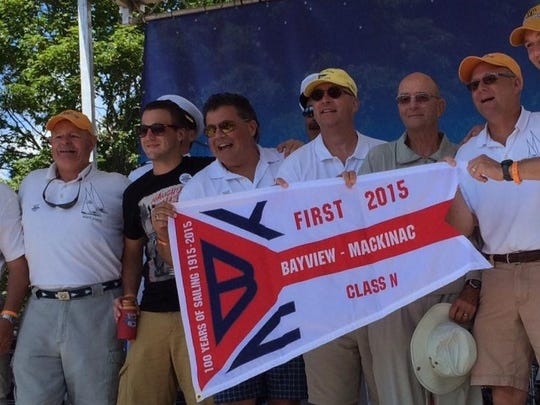 Members of the crew received their championship flag and celebrated their victory at the July 21 awards ceremony on Mackinac Island. Crew members are (from left) Ed Ely, Rick Birdsall, Cameron Benedict, Chris Benedict, Win Cooper III, Win Cooper, Steve Bradley and Dale McNabb.