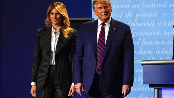 President Donald Trump stands on stage with first lady Melania Trump after the first presidential debate Tuesda in Cleveland. President Trump and first lady Melania Trump have tested positive for the coronavirus, the president tweeted early Friday.