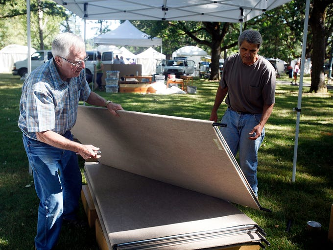 Skip Eshleman, left, of Amity, helps artist Steve Tyree, of Amity, set up his sculpture booth at the Salem Art Fair, Thursday July 17, 2014. Eshleman, who was a coordinator of the fair years ago, is now volunteering his time.