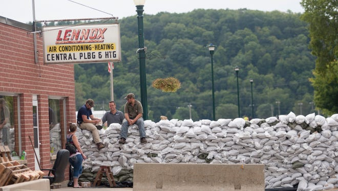 Volunteers rest on sandbags, which were erected the prior day, as the Turkey River swells causing flood damage to the basements of nearby businesses in Elkader, Iowa, on Friday, Aug. 26, 2016.